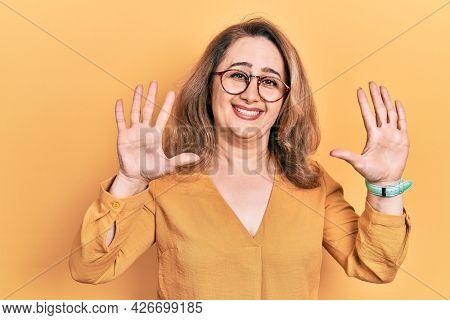 Middle age caucasian woman wearing casual clothes and glasses showing and pointing up with fingers number ten while smiling confident and happy.