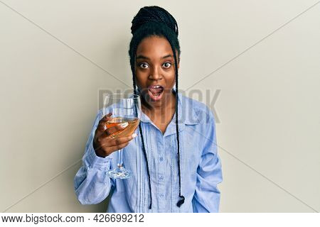 African american woman with braided hair drinking a glass of white wine scared and amazed with open mouth for surprise, disbelief face