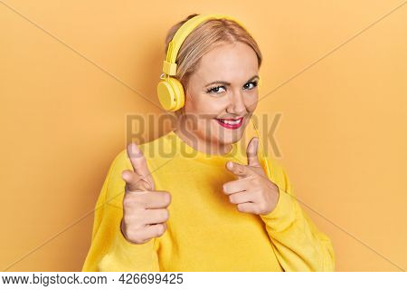 Young blonde woman listening to music using headphones pointing fingers to camera with happy and funny face. good energy and vibes.