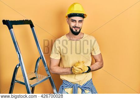Handsome man with beard by construction stairs wearing hardhat with hands together and crossed fingers smiling relaxed and cheerful. success and optimistic