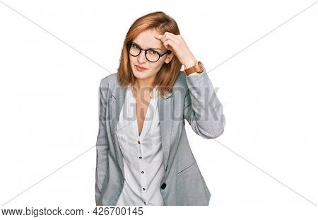 Young caucasian woman wearing business style and glasses pointing unhappy to pimple on forehead, ugly infection of blackhead. acne and skin problem