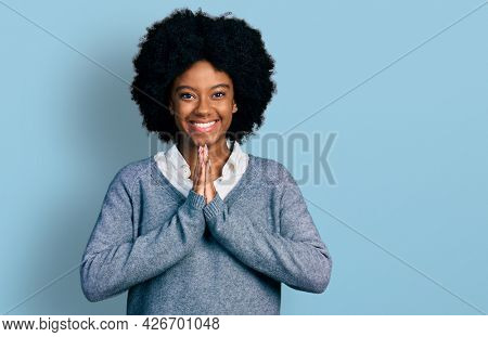 Young african american woman wearing business clothes praying with hands together asking for forgiveness smiling confident.