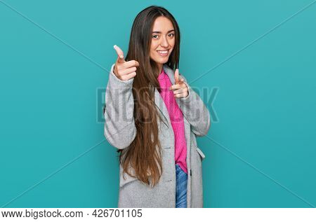 Young hispanic girl wearing business clothes pointing fingers to camera with happy and funny face. good energy and vibes.