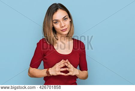 Young blonde girl wearing casual clothes hands together and fingers crossed smiling relaxed and cheerful. success and optimistic