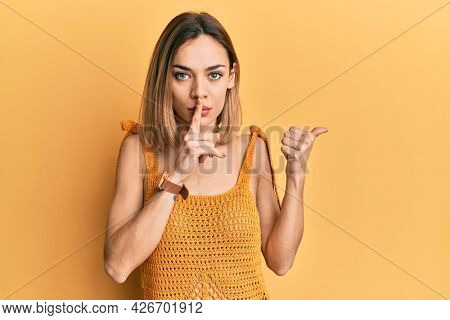 Young caucasian blonde woman wearing casual yellow t shirt asking to be quiet with finger on lips pointing with hand to the side. silence and secret concept.