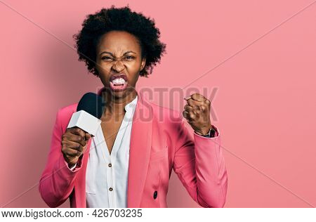 African american woman with afro hair holding reporter microphone annoyed and frustrated shouting with anger, yelling crazy with anger and hand raised