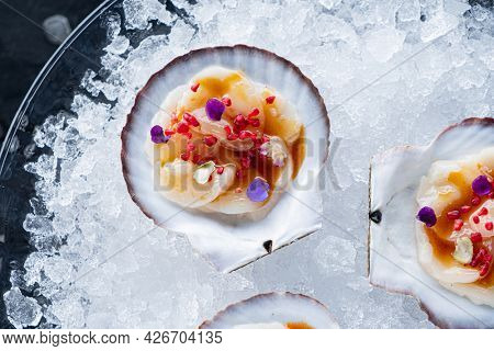 Freshness of oysters on a stone board. Opened oysters shells for freshness. Two half-opened shellfish with lemon and lime on black stone background.