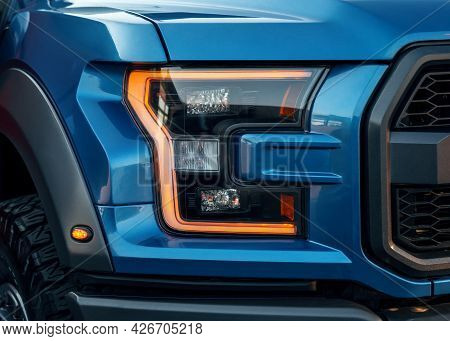 Front Illuminated Headlights Of A Blue Modern Suv Car. Close Up Detail On One Of The Led Headlights