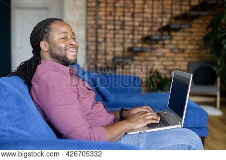 Inspired African-american Man Using Laptop Sitting On The Couch At Home, Cheerful Biracial Guy With