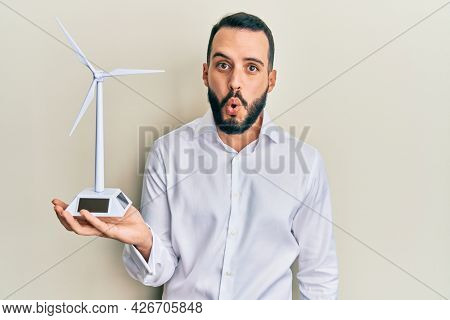 Young man with beard holding solar windmill for renewable electricity scared and amazed with open mouth for surprise, disbelief face