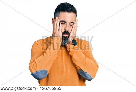 Hispanic man with beard wearing casual winter sweater tired hands covering face, depression and sadness, upset and irritated for problem