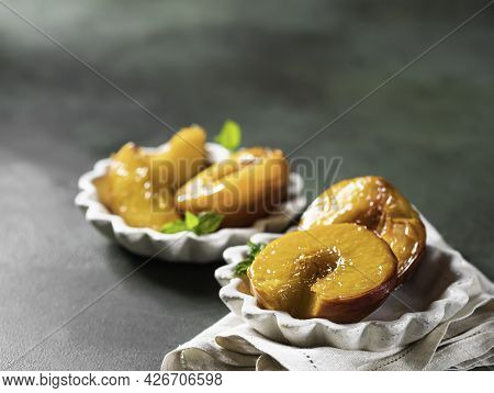 Caramelized Peaches With Honey, With Mint Leaves On A Concrete Background With Shadows. Summer Desse