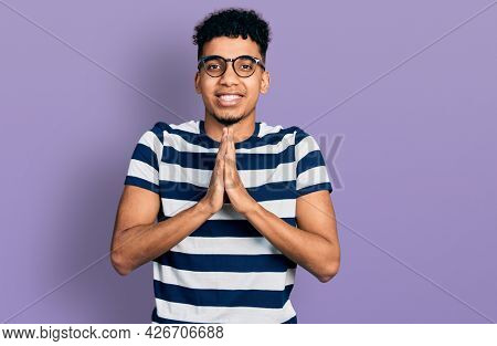 Young african american man wearing casual clothes and glasses praying with hands together asking for forgiveness smiling confident.