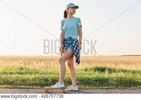Full Length Portrait Of Slim Sporty Woman Wearing T Shirt And Visor Cap, Standing With Leg On Skateb