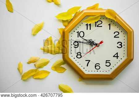 Clock Time With Dry Yellow Leaves On White Background. Flat Lay With Free Space. Autumn Season, New