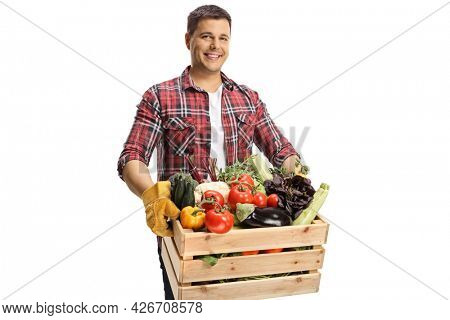 Farmer holding a crate with vegetables and looking at camera isolated on white background