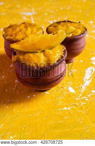 Closeup Of Mango Pulp In Earthen Bowls With Ripe Mango Cut Isolated On Yellow Background In Vertical
