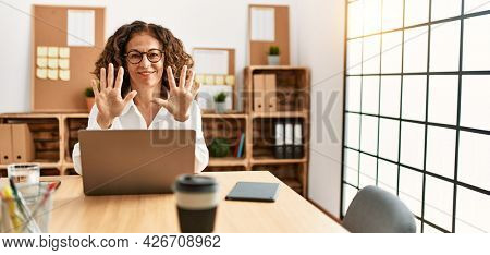 Middle age hispanic woman working at the office wearing glasses showing and pointing up with fingers number ten while smiling confident and happy.