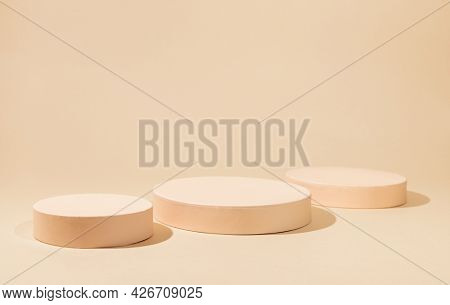 Abstract background with geometric podiums or pedestals for products presentation or exhibitions. Empty cylinder podiums on pastel backdrop.