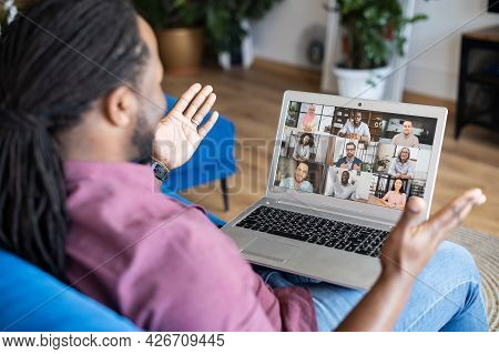 African Guy Taking A Part In Online Webinar, Video Conference, Talking And Discussing With A Group O