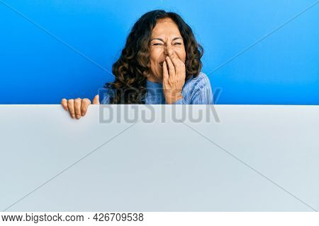 Middle age hispanic woman holding blank empty banner laughing and embarrassed giggle covering mouth with hands, gossip and scandal concept