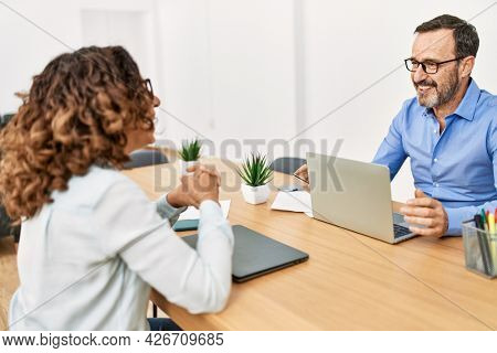 Two middle age business workers smiling happy talking at the office.