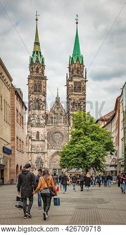 Nuremberg, Germany - May 17, 2016: Karolinenstrasse street with walking people and St. Lawrence church in Nuremberg
