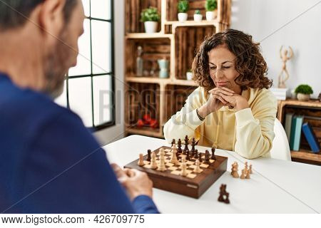 Middle age hispanic couple concentrated sitting on the table playing chess at home.