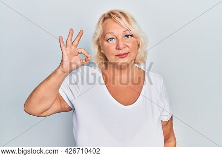 Middle age blonde woman doing ok positive gesture relaxed with serious expression on face. simple and natural looking at the camera.