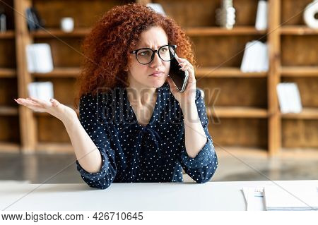 Confused Puzzled Brunette Woman With Curly Hairstyle Talking On The Cell Phone And Expressing Misund