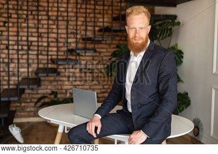 Successful Red-haired Businessman In Formal Suit Leaned On The Table In Relaxed Pose And Looks At Th