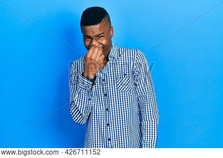 Young african american man wearing casual clothes smelling something stinky and disgusting, intolerable smell, holding breath with fingers on nose. bad smell