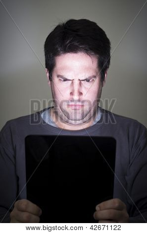 Man Stares Intently At A Tablet Device