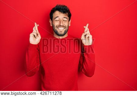 Handsome man with beard wearing casual red sweater gesturing finger crossed smiling with hope and eyes closed. luck and superstitious concept.