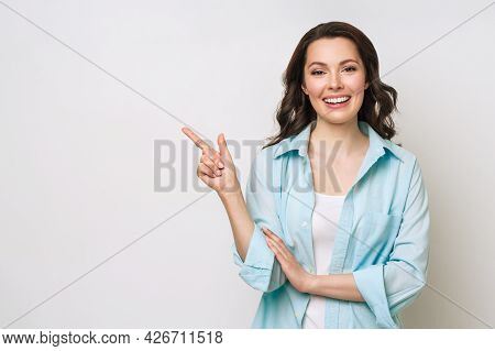 Young Woman Smiling And Gesturing To Copy Space.