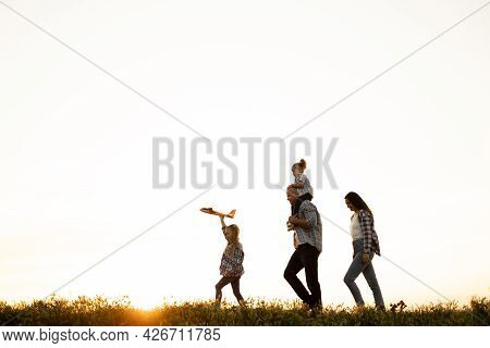 Family Of Tourists Walking At Sunset Across The Field In Summer Silhouettes Of Dad Mom And Daughters