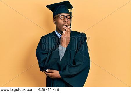 Young african american man wearing graduation cap and ceremony robe bored yawning tired covering mouth with hand. restless and sleepiness.