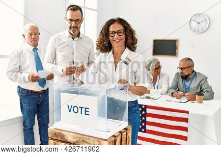 Middle age american voter woman smiling happy putting ballot in voting box at vote center.