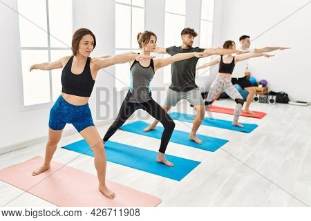 Group of young hispanic people concentrate training yoga at sport center.
