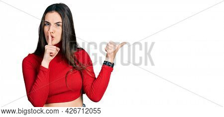 Young brunette teenager wearing red turtleneck sweater asking to be quiet with finger on lips pointing with hand to the side. silence and secret concept.