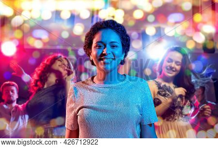 leisure, clubbing and nightlife concept - smiling young african american woman over ultraviolet neon lights over people dancin at nightclub background