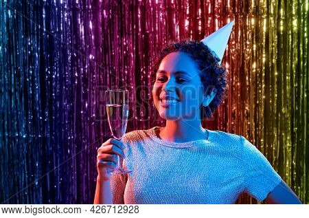 birthday, celebration and nightlife concept - happy smiling young african american woman in party cap with glass of champagne in ultraviolet neon lights over rainbow foil curtain background