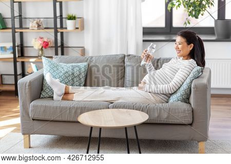 pregnancy, rest, people and expectation concept - happy smiling pregnant asian woman sitting on sofa at home and drinking water from reusable glass bottle