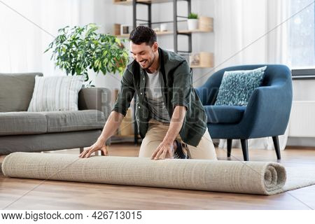 household, home improvement and interior concept - happy smiling young man unfolding carpet