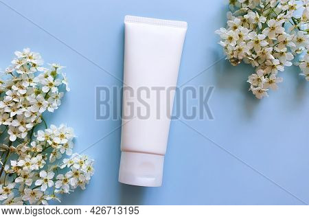 Unbranded White Cosmetic Squeeze Tube And Spring White Flowers Of Bird Cherry On Blue Background. Mo