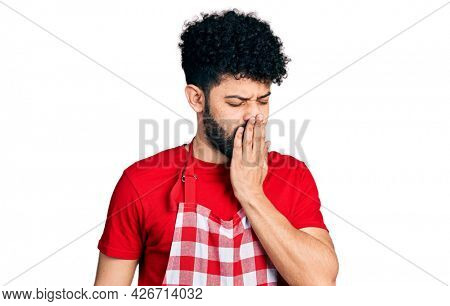 Young arab man with beard wearing cook apron bored yawning tired covering mouth with hand. restless and sleepiness.