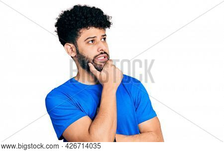 Young arab man with beard wearing casual blue t shirt thinking worried about a question, concerned and nervous with hand on chin