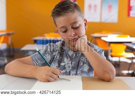 Caucasian schoolboy sitting at desk in classroom drawing with pencil in book. childhood and education at elementary school.