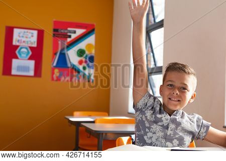 Happy caucasian schoolboy sitting at desk in classroom raising hand during lesson. childhood and education at elementary school.