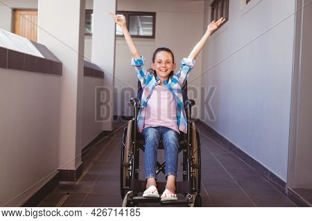 Portrait of smiling disabled caucasian schoolgirl sitting in wheelchair raising arms in corridor. childhood and education at elementary school.
